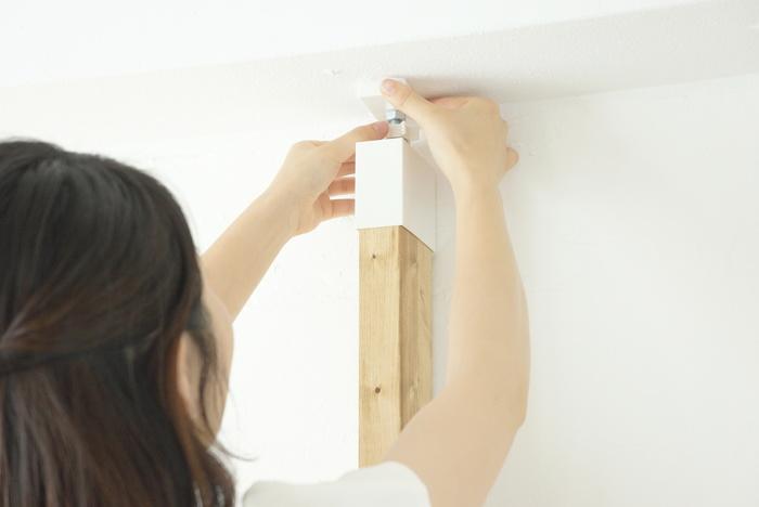 天井との接点は突っ張り棒式になっているから簡単で分かりやすい。木材の上下にパーツを取り付けたら、上部で調整します。壁に釘を打ったりしないから、取り外しても穴が残らずきれいなままです。