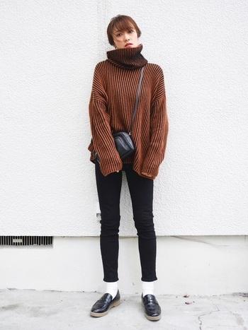 冬に大活躍のニットと細身のパンツは相性抜群の組み合わせ。首元にボリュームのある存在感のあるリブニットには、すっきりとした黒のパンツを合わせ、さらにヘアスタイルもまとめることで、メリハリのある着こなしになります。