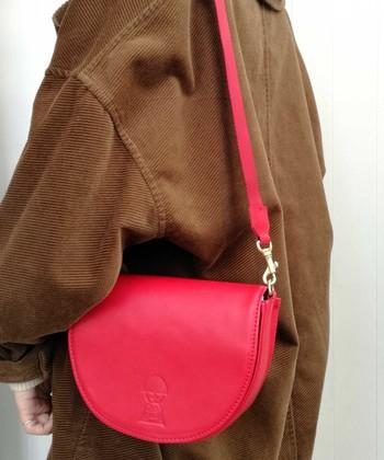 高級感のある牛皮素材を使用しながらも、ストラップにはナイロンを使うことで気取らない印象に仕上げた小さなバッグ。気分の弾むポップな赤でちょっとしたお出かけを楽しく。
