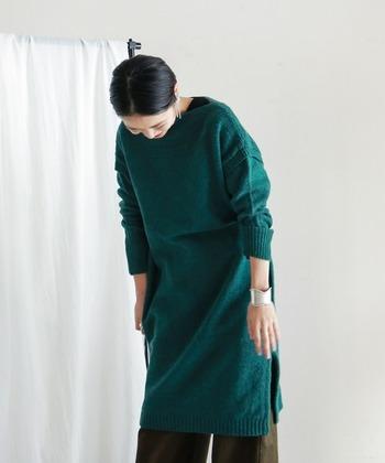 クリスマスのモミの木のような、ぬくもりある明るさを持つグリーンのニットワンピース。肩や袖部分で編み目を切り替えてあるので、誰でも着こなしやすいシルエットに。