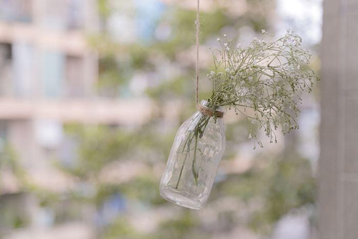 ヴィンテージのガラスボトルにお花を生けて、麻ひもで吊るしています。ナチュラルな雰囲気が楽しめる窓際になりました。