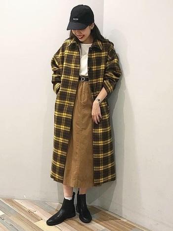 イエローチェックのコートが主役のコーデの名わき役に、コーデュロイのスカートを。スカート丈とコート丈のバランスも絶妙です。