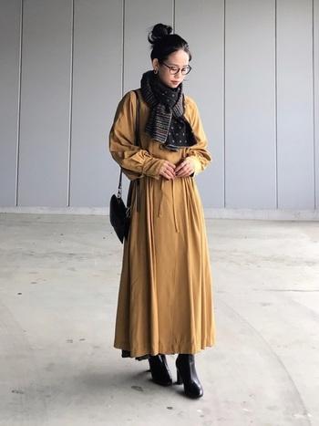 羽織にもなる万能なワンピースは、モードなデザインなので黒小物を合わせて統一感をプラス。
