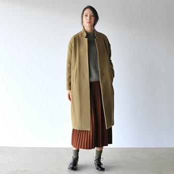 こっくりブラウンのプリーツスカートが主役になるよう、他のアイテムは淡い色で統一。端正なベージュのコートを羽織ったら、エレガントとマニッシュが共存する着こなしに。