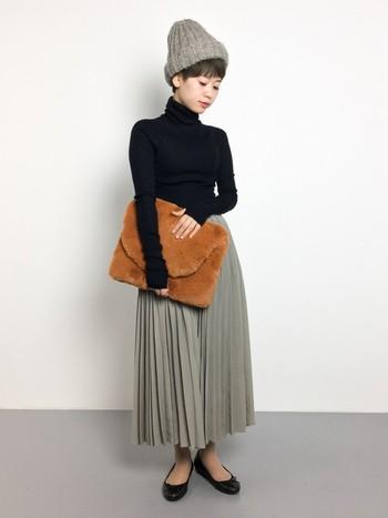 いたってシンプルな、ニットとプリーツスカートの着こなし。それでも旬度ばっちりに見えるのは、存在感大なもこもこバッグとメンズライクなニット帽のおかげ。