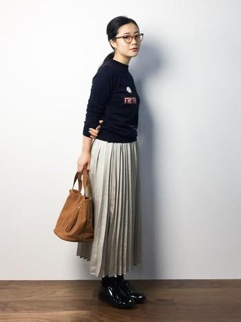 フェミニンな細プリーツのロングスカートは、ロゴ入りトップスと大きな黒縁めがねでボーイッシュに。エナメルのレースアップシューズで足元にもしっかりポイントを。