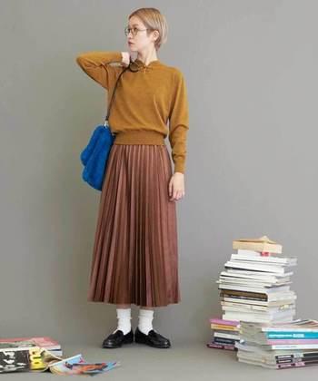 からし色のニットに薄いブラウンのスカート、肩にはブルーのショルダーバッグ。意表を突く配色で、コーディネートに遊び心と新鮮味を。