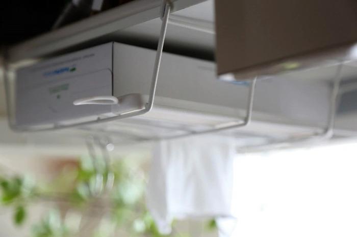 収納の追加は、収納棚の中に限ったことではありません。こちらの画像は吊戸棚にセリアのワイヤーラックをつけたものです。ラップなどを収納したり、またキッチンで使いたくても濡れないか気になるティッシュもケースを逆さに収納すれば、ワンアクションで使えて便利ですね。