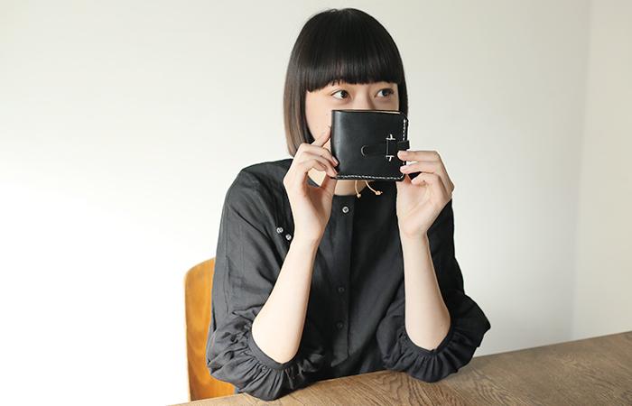 シンプルなのに洗練された印象を与える、黒の二つ折りレザー財布。コンパクトだから、ミニバッグやポシェットに忍ばせるのも◎