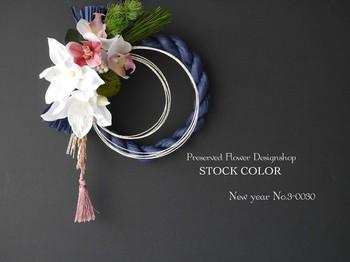 ブルーのしめ縄に優しいピンク色がよく映えた個性的なしめ飾り。お花もコチョウランとユーチャリスが組み合わされていてとても華やかです。