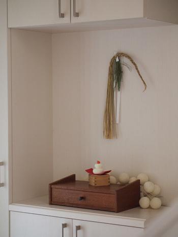 玄関の飾り棚に小ぶりの鏡餅と一緒に。おうちのインテリアに合わせて、今年は色や飾りをおさえてシンプルにまとめてみるものいいかもしれませんね。