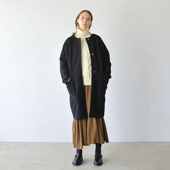 ネイビーのノーカラーコートは、ナチュラルコーデと相性抜群のアイテム。白のケーブルニットとベージュのロングスカートを合わせて、ほっこり冬らしい着こなしに仕上げています。