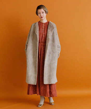ゆったりシルエットのノーカラーコートは、深みのあるオレンジのワンピースと合わせてこなれ感たっぷりに。フェイクファーが季節感をアピールしてくれるので、どんなワンピースに羽織っても今っぽく着こなせますよ。