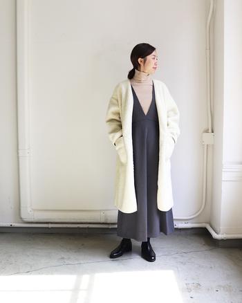 ネイビーのワンピースとベージュのインナーを合わせたラフコーデに、白のノーカラーコートを羽織ったスタイリングです。ベーシックなカラーのみを使った着こなしは、秋冬らしさと安心感を与えてくれますね。