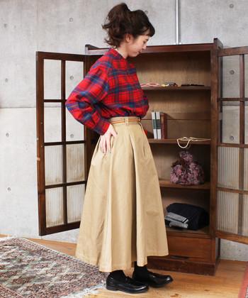 一年を通して活用できる、チノ素材のベージュスカート。赤のチェック柄シャツで季節感を取り入れつつ、足元は黒のシューズでキュッとお大人っぽく引き締めています。