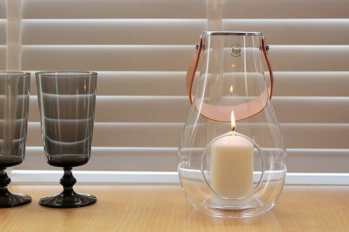 【 HOLMEGAARD(ホルムガード)/デザイン ウィズ ライト ランタン 】 屋外用ランタンは主に照明器具としての明るさを重視しますが、あたりをほのかに照らす蝋燭のランタンは、穏やかな安らぎのひとときを演出してくれます。こちらは伝統的な吹きガラス製法を用いた雫型のランタン。天然皮革のキャリーストラップ付きで手軽に持ち運びできます。特別な日のテーブルコーディネートに使っても素敵ですし、蝋燭の代わりに小さな観葉植物を入れてインテリアにするのもおすすめです。