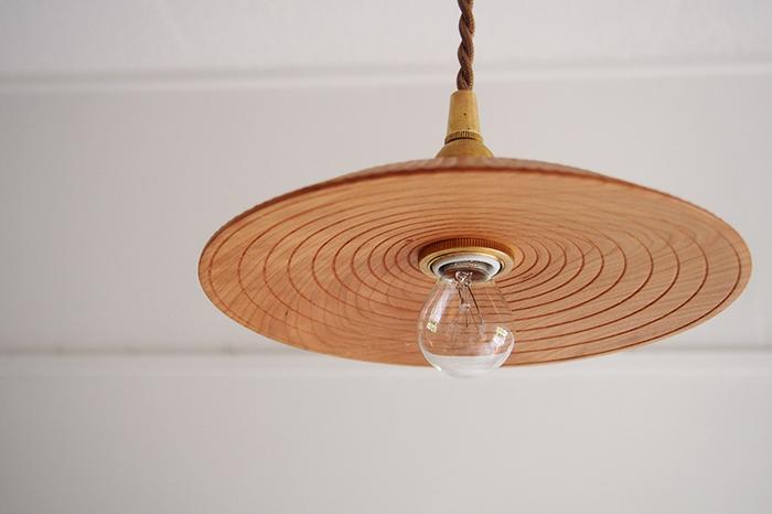 木のぬくもりが優しい、作家ものの手彫りのランプシェード。外側と内側で彫り方を変えて、豊かな表情をつけています。木と真鍮、そし電球の灯り…異素材がひとつに調和して、お部屋の中に癒しの空間を作り出します。