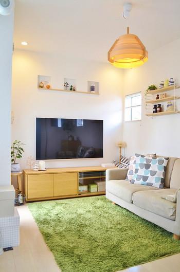 床や壁が白ベースのリビングに、グリーンのラグを敷いてアクセントを効かせています。北欧テキスタイルのクッションカバーや北欧雑貨で彩れば、ほっこりした癒し空間に。