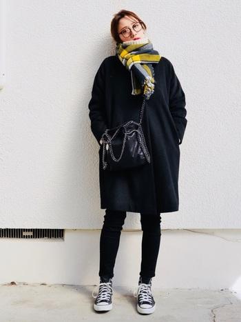 ダークトーンのコートは、ビビッドカラーの小物とも好相性。マフラー以外を黒のワントーンでまとめ、イエローのタータンチェックマフラーを差し色として際立たせています。