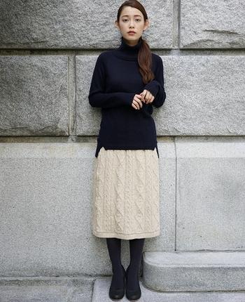 ベージュのニットタイトスカートに、ネイビーのハイネックトップスを合わせたコーディネートです。タックインして着こなしても良いですが、あえて裾を出すのが今年っぽいスタイリングに。