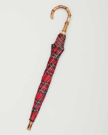 バンブーの持ち手がおしゃれな長傘も、トラディショナルウェザーウェアの定番アイテムです。ブランドロゴをあしらった持ち手のゴールドプレートと、クラシカルなチェック柄が上品な雰囲気ですね。シンプルなコーディネートのワンポイントとしても活躍してくれます。