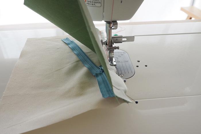 """ポイントはファスナー用のミシンの""""押さえ""""を使うこと。ファスナーのスライダーがぶつかると縫い目が曲がってしまうので、ミシン針を刺した状態のまま、途中で一旦押さえを上げて、スライダーを縫い終わった方へ移動させます。焦らずゆっくり縫って、きれいに仕上げましょう。"""