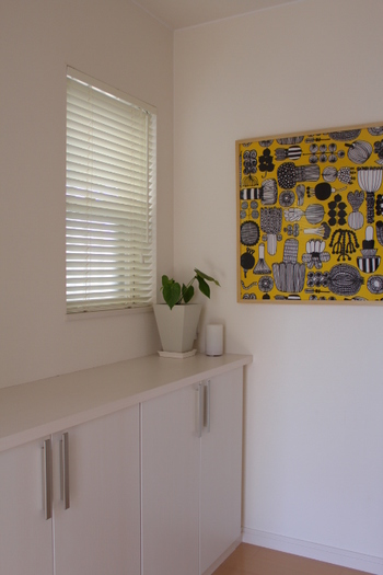 黄色をベースにしたファブリックで、明るくフレッシュな玄関に。緑を飾るのも、玄関を心地いい空間にする定番テクニックです。