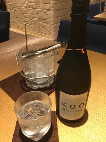 オリジナル麦焼酎「KOO」。  お食事の精算は、腕にはめたリストバンドからバーコードを読み取ってもらい、退館時にまとめて支払うシステム。