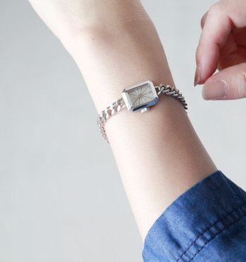 光がきらめくように四方に広がった文字盤が手元に美しさをプラスしてくれる、シルバーの腕時計。華奢なチェーンのベルトは、程よくマニッシュな雰囲気に。