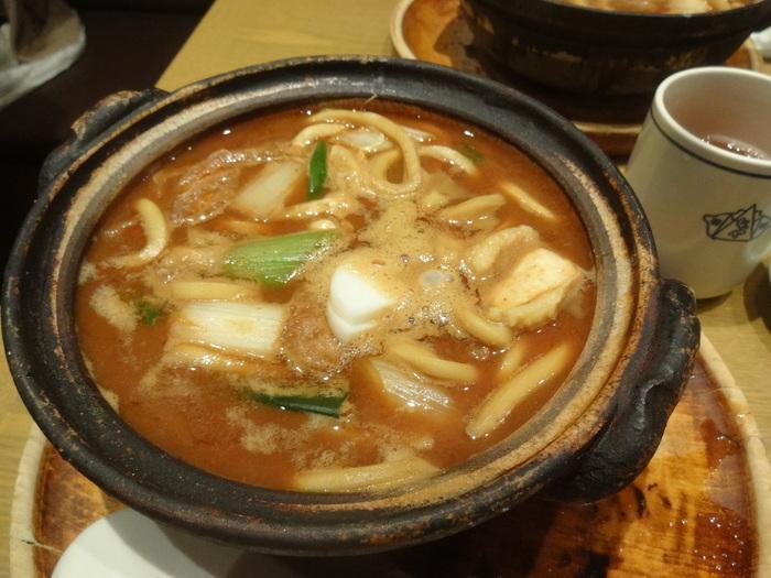 土鍋で熱々に煮立った状態で提供されるみそ煮込みうどん。土鍋の蓋に一度うどんを移して、ほんの少し冷ましてからいただくのが本場の食べ方なのだとか。