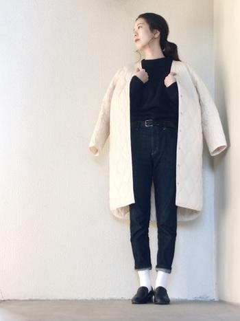 黒ニット&濃紺デニムの、ダークトーンで統一した上下にオフホワイトのコートで明るさをプラス。足元に白ソックスを合わせることで、コートが浮かないようバランスを取っています。