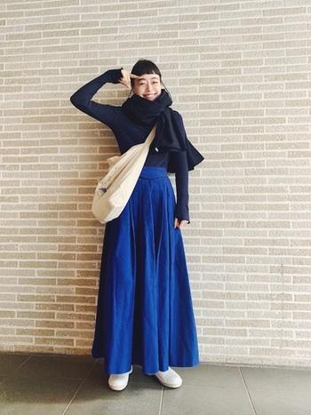 シックなネイビーのニットは、ブルーのロングスカートで華やかに。スカートの丈がかなり長いので、トップスINとマフラーで重心をアップ。