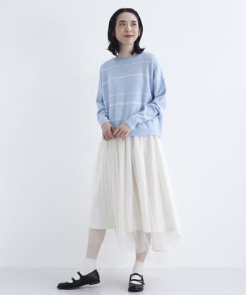 甘さだけが立ってしまいそうなホワイトのエアリースカート。大人らしく着こなしたいなら、トップスは落ち着きのある淡ブルーのニットで。