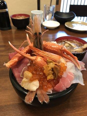 「魚屋の台所」の海鮮丼は、豪快な盛り付けでも有名です。テンションが高まりますね。  人気なのは、店主にお任せスタイルの海鮮丼。ネタはその日の仕入れによりますが、うに、イクラ、マグロ、鯛、ヒラメ、ボタン海老、ズワイガニ、イカ、タコなど・・。さらにはサービスが付くことも?! 上・並・小から選べますが、ご飯の量は変わらないとこのとです。  あわせてカニ汁もいただけば、幸せ気分この上なしですね♪