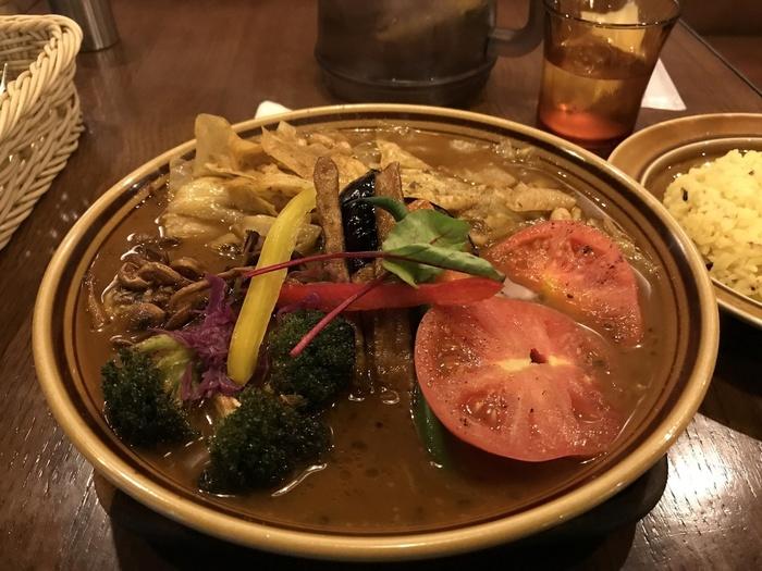 こちらは、「どっさり1日分の野菜」という名前のスープカレーメニュー。その名の通り野菜がたっぷり使われていて、ヘルシーで栄養もしっかり。女性に嬉しい一品です。 こちらのメニューに、チキンレッグなど、お肉をトッピングしていただくのも、人気ですよ。