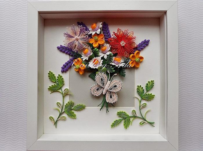 いろんなパーツを組み合わせて作られた、さまざまな種類のお花のブーケ。まるで本物のような繊細な作りです。周りに飾られた蝶や葉っぱもペーパークイリングで作られています。