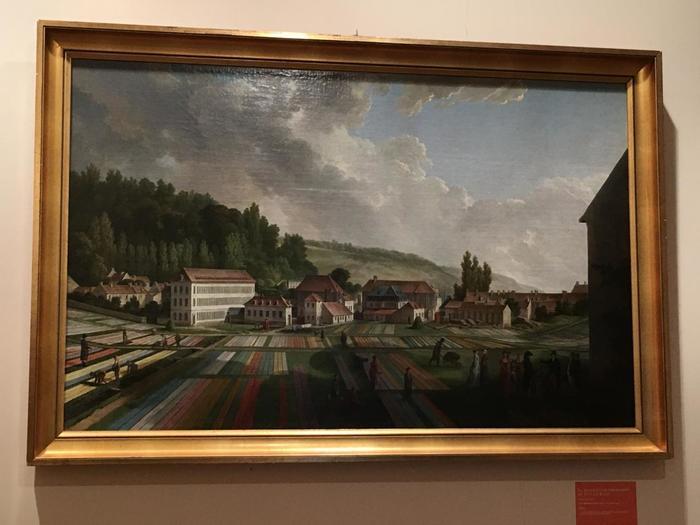 オーベルカンフは1760年、ジュイ=アン=ジョザスに工場を創業し、全盛期には1300人以上もの従業員を雇用。またすべての工程において研究熱心で、デザインは有能な画家たちに依頼するほどのこだわりようでした。  そして、画家、ジャン=バティスト・ユエを、主任デザイナーに起用したことで、この工場ならではの生地の魅力(=トワル・ド・ジュイ)が花開くこととなります。この二人が揃わなければ、後世に残される布文化には発展しなかったかもしれません。