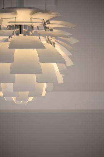 【 PH Artichoke(アーティチョーク) 】1958年 比類のない存在感で名作照明としての地位を不動のものにした「 アーティチョーク」。微妙にカーブした72枚のシェードが、絶妙な間接光で器具自体をふんわり浮かび上がらせます。誰もがどこかで目にしたことのある印象的なデザインは、明かりを消している姿でさえ美しく、世界で最も有名な照明器具と言っても過言ではない逸品です。