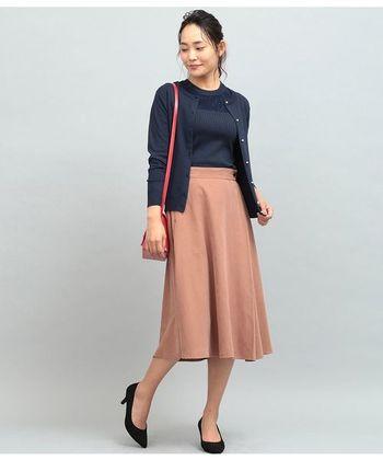 カーディガンは、落ち着いたベーシックカラーを選びましょう。紺色のカーディガンにくすみピンクのスカートを合わせれば、女性らしくきちんとした印象に仕上がります。