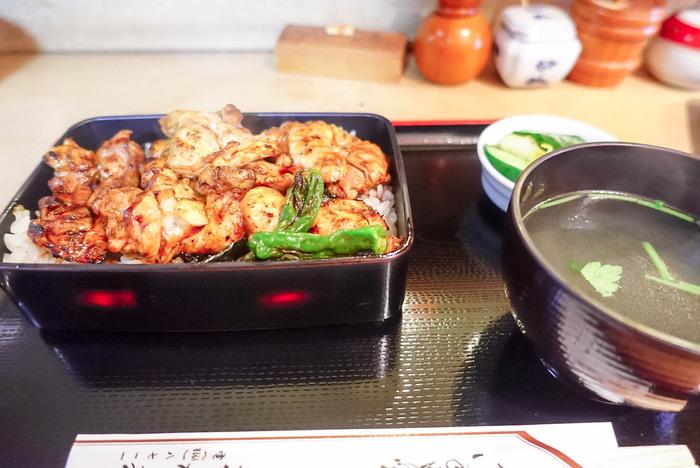 ランチは「焼き鳥重」の1品のみ。炭火で焼かれた鶏肉に、長年継ぎ足してきた秘伝のタレがたっぷりかかっています。旨みの強い鶏肉は香ばしく、ジューシー。お重いっぱいにお肉がのっていてボリュームも満点です。