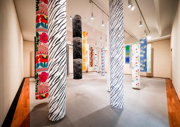 こちらの展示空間は、それぞれのテキスタイルが、一本の木のよう。まるで森にいるような感覚になれますね。  手前には、1992年発表の「Suuri Taiga[大草原]」。そして左端には、色あざやかな「Kuja(路地)」がちらり。1976年発表の作品で、お花に加え、にわとりも可愛らしいですね。