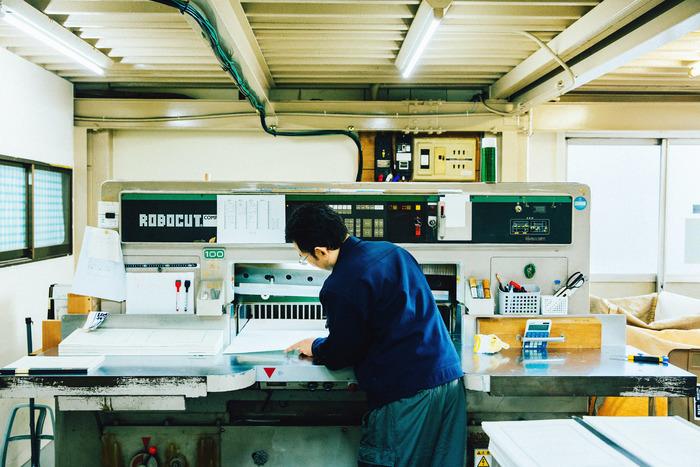 まずは、裁断機という機械で紙をカットします。製品のサイズなどは機械にあらかじめ入力されているため、自動で裁断されていきます