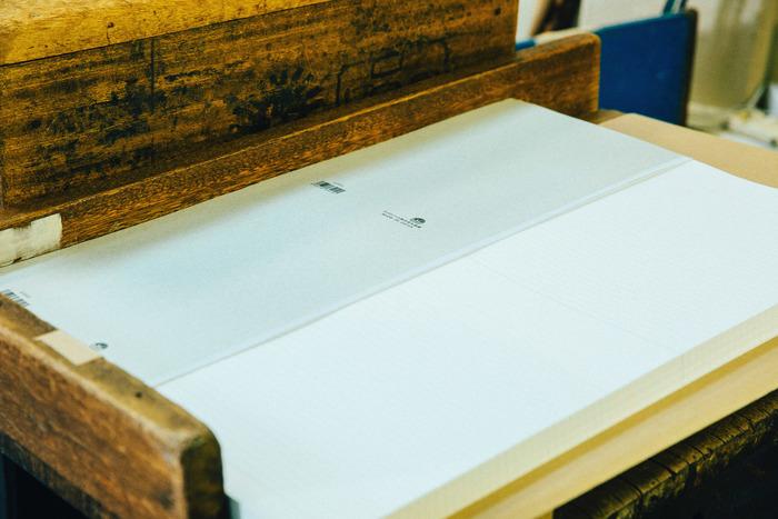 今回製造工程を見せていただいたのは「特A10」という、厚みがある100枚単位のノート。さきほどの紙の束を因数機という機械で数え、25枚ごとに仕切り(付箋)を入れます。その後、木型にセットし、表紙を重ねていきます