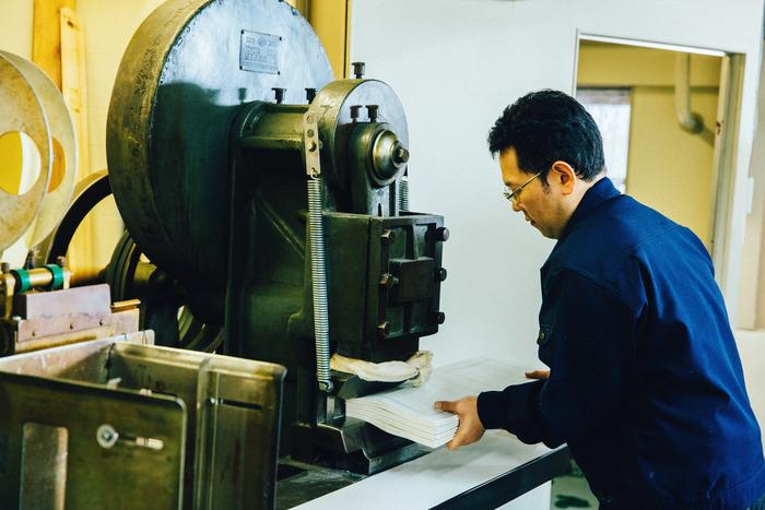 「均し機」と呼ばれる機械で背を平らにする作業。スタンプのような動きをするマシンに、位置をずらしながら素早く紙を挟みます。均等に紙を潰していくために、紙をしっかりと奥につけることが大切です
