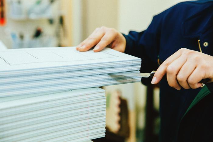 背固めの糊で固まっている束を、一冊ずつ包丁で切り離していきます