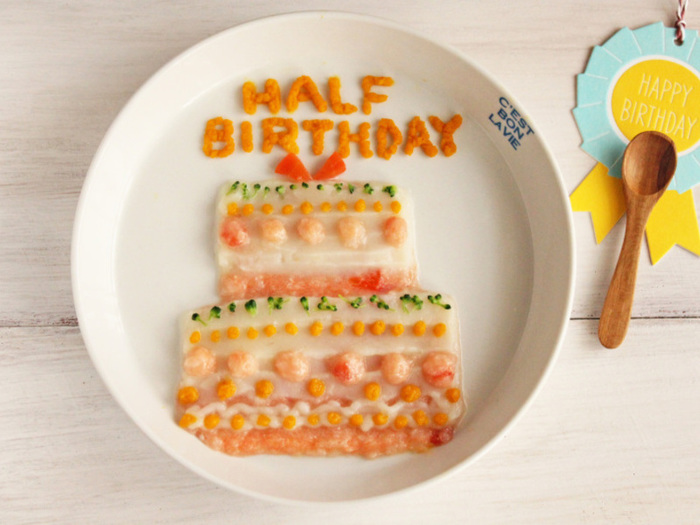 さっそくコルネを使って、プレートをつくってみましょう。こちらでは、お馴染みの離乳食「10倍がゆ」をケーキ型に平たくお皿にしいて、その上にケーキの模様を描いています。ブロッコリーは緑、ニンジンはオレンジ色として、上手に活用されていますね。  好きなキャラクター、おめでとうの言葉や、名前。また、ママが好きなデザインを描いてみましょう。写真に残してあげて、大きくなったら見せてあげられるといいですよね。