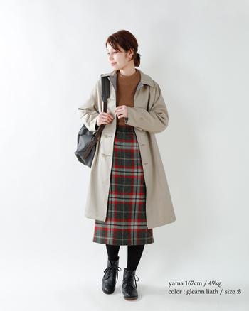 赤のラインが効いたスカートはベージュのコートを合わせて軽やかに。明るめブラウンのニットを合わせると可愛らしい、けれど品のあるトラッドコーデに。
