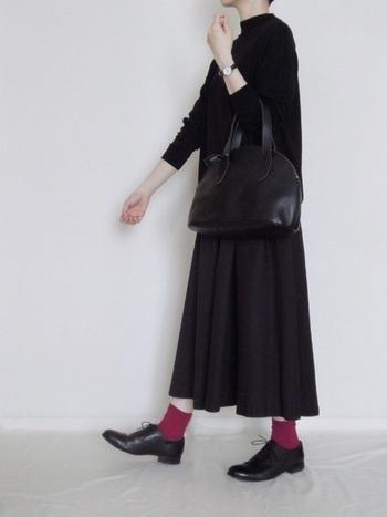 オールブラックコーデに赤い靴下。かっこよさとかわいらしさが上手く共存しているスタイル。