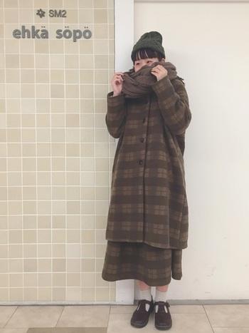 チェック柄がかわいいロング丈のステンカラーコートにちらっと同じ柄のスカートが覗いています。深いブラウンカラーで、総柄でも落ち着いた印象です。 ニットキャップやもこもことしたストールを巻いて、防寒対策もばっちりですね。外のお出かけも怖くない、あったかコーディネートです。