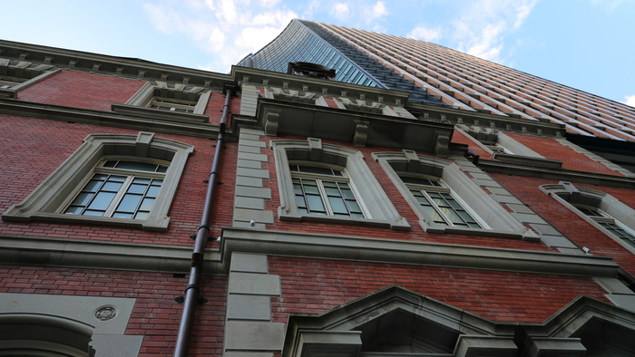 この界隈が、現在の姿へと変貌を遂げる契機となったのは、三菱による最初のオフィスビル「三菱一号館」の竣工と、それに続く赤煉瓦街の建設です。  1914年には、三河吉田藩など三藩の屋敷跡地が「東京駅」として開かれ、その5年後に「丸ビル」が完成。当地は、日本を代表するビジネス街として、急速に発展していきました。  【赤煉瓦の外壁が魅力的な「三菱一号館美術館」は、建設当時のままに細部にわたって復元させた美術館。後方にそびえるのは、隣接する34階建ての「丸の内パークビルディング」。】